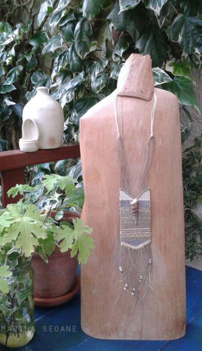 collar textil presentado en base de madera
